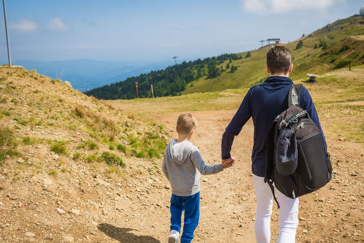 Rear view of father and son holding hands while walking on land