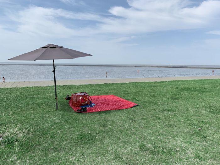 View of umbrella on beach against sky