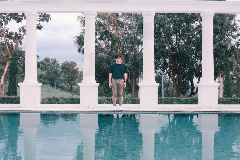 Rear view of man standing by swimming pool