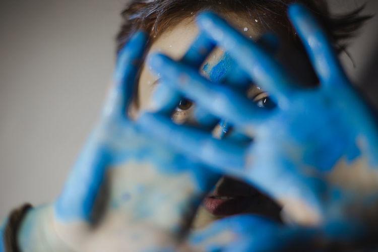 Close-Up Portrait Of Woman Showing Blue Paint On Palms