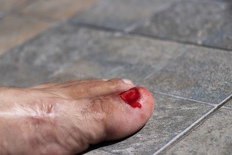 Close-up of hand holding red leaf on tiled floor
