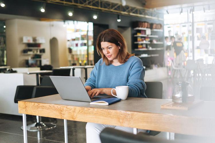 Beautiful stylish young woman plus size body positive using laptop at the beauty salon office