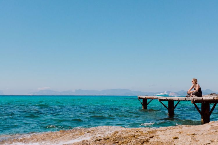 EyeEm Selects Copy Space Blue Clear Sky Sea Water Tranquil Scene Outdoors Nature Beauty In Nature One Person Scenics Day Real People Tranquility Full Length Relaxation Sky People Adult Women Beauty In Nature Formentera Es Moli De Sal Blue Water Lost In The Landscape