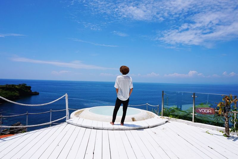 Rear view of man standing on wooden deck at resort against sea