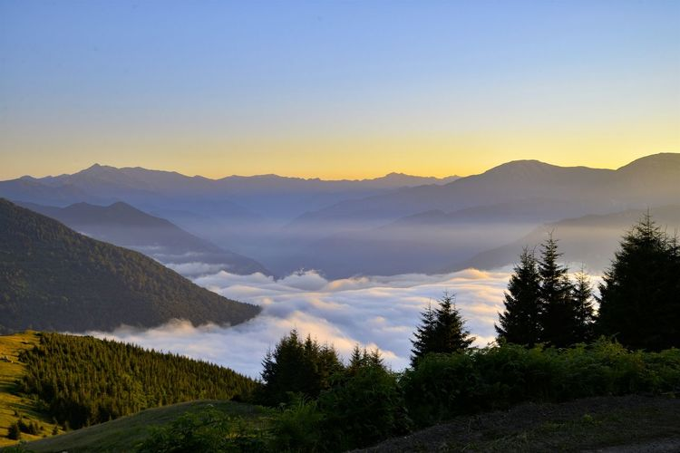 Scenic view of cloudscape amidst mountains during sunset