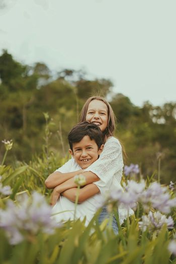 Portrait of smiling brother and sister standing on field amidst plants