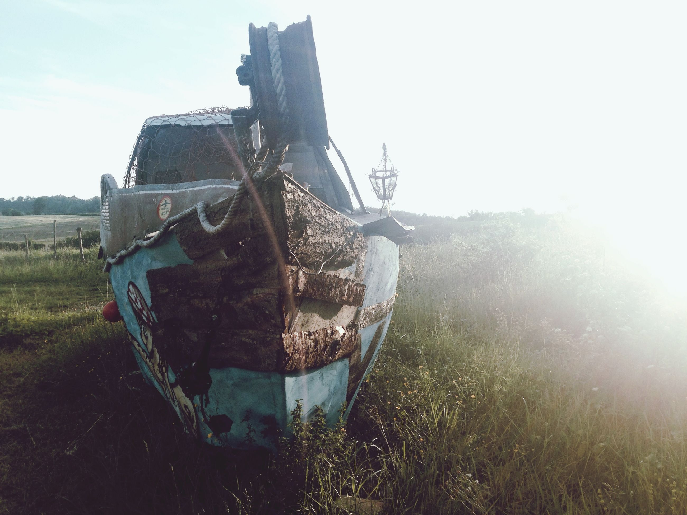 sky, field, clear sky, sunlight, grass, abandoned, damaged, day, landscape, built structure, outdoors, rural scene, nature, architecture, building exterior, obsolete, run-down, tranquility