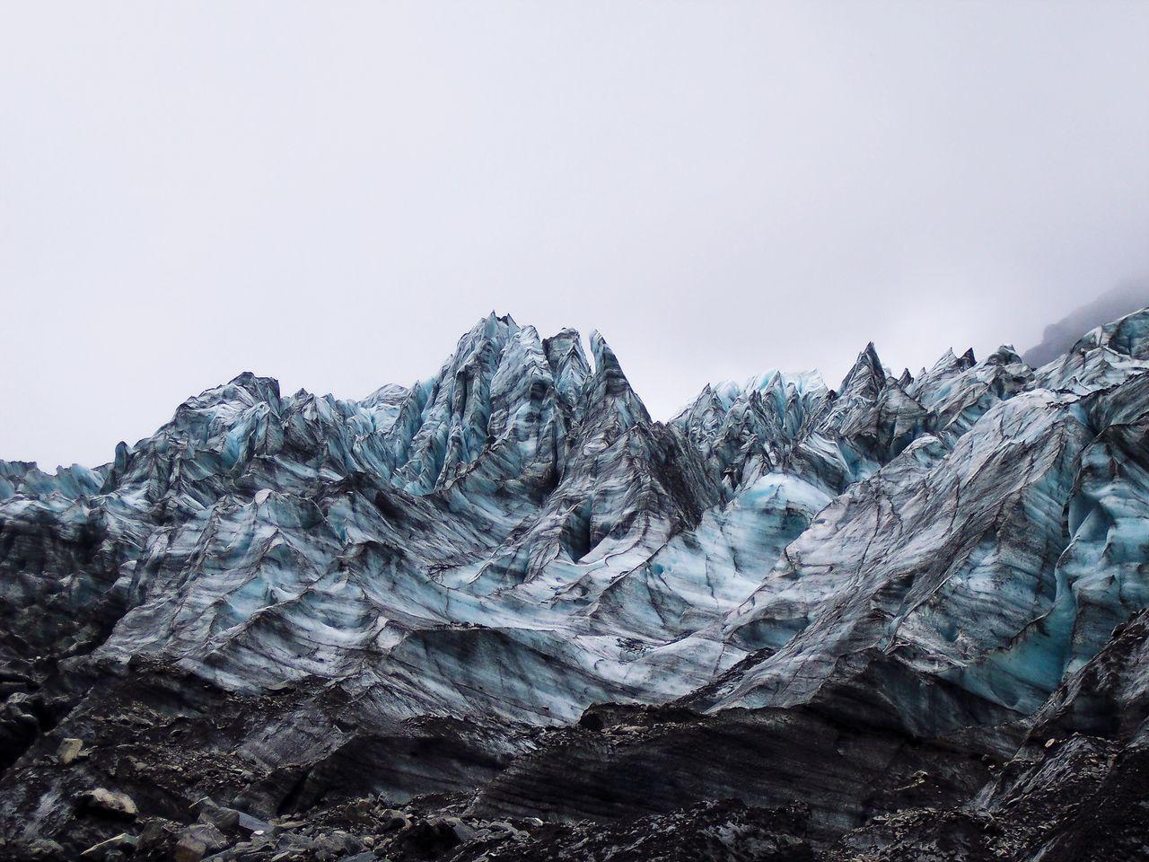 Low angle view of frozen glacier landscape against sky
