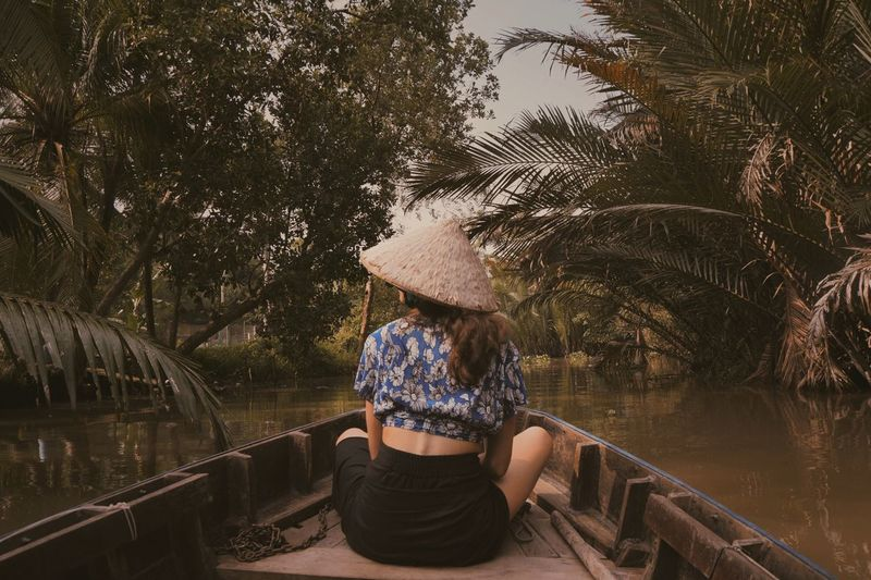 Rear view of woman wearing asian style conical hat sitting on rowboat in lake