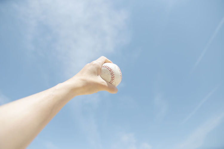 Cropped Hand Holding Baseball Against Sky