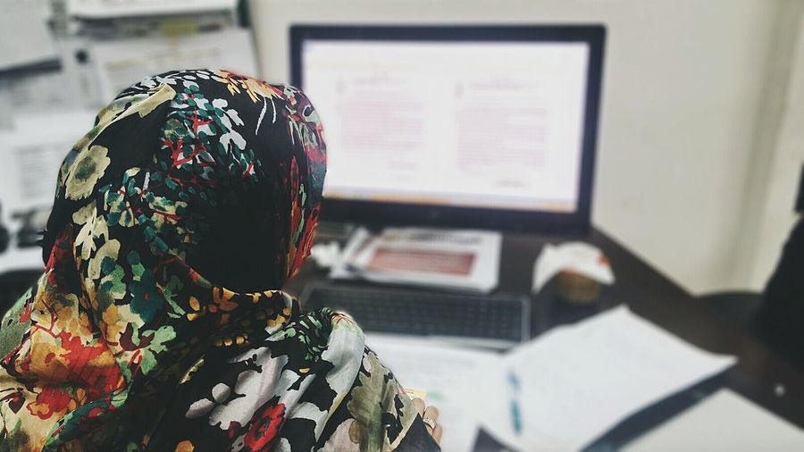 Rear view of businesswoman wearing hijab using computer at office