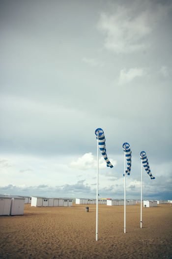 Windsocks on beach against sky