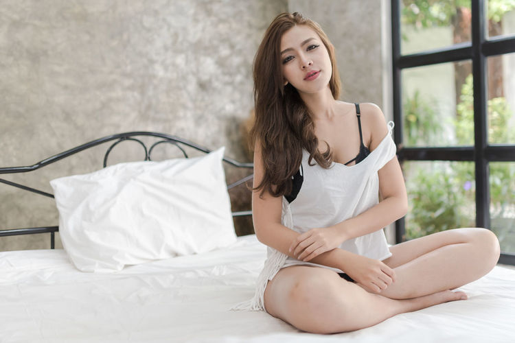 One Person Young Adult Bed Furniture Young Women Beauty Beautiful Woman Sitting Lifestyles Indoors  Full Length Women Real People Adult Relaxation Long Hair Hairstyle Lingerie Contemplation