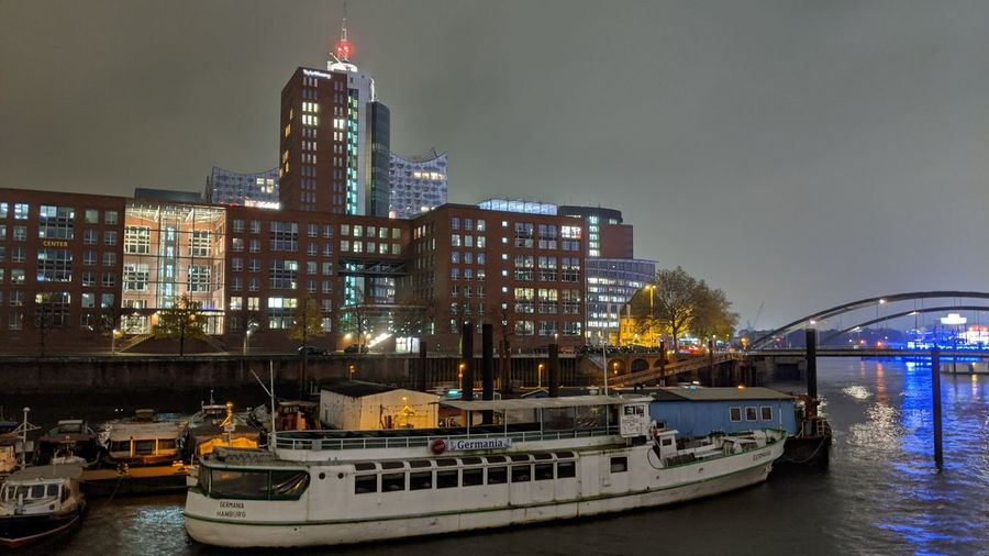 Boats in river by illuminated buildings against sky at night