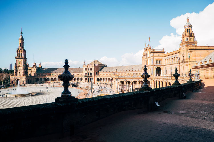 Historic buildings at plaza de espana against blue sky