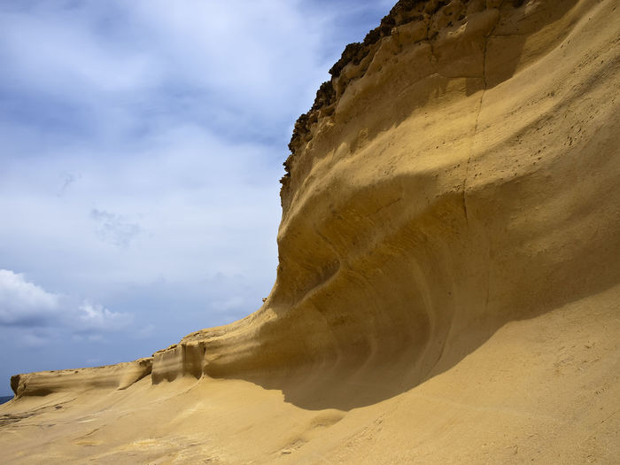 Low Angle View Of Sand Dunes Against Cloudy Sky