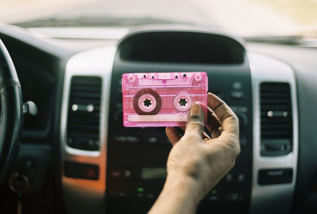 Cropped hand of person holding audio cassette in car