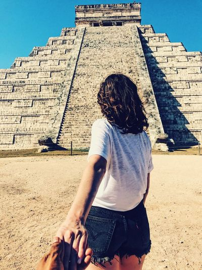 Cropped Hand Of Man Holding Woman Standing Against Pyramid