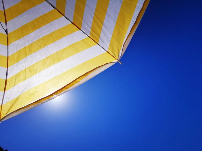 Low angle view of yellow flag against clear blue sky