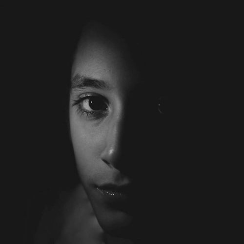 Close-up portrait of serious young woman against black background
