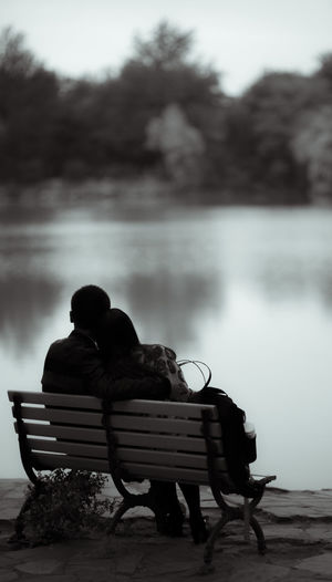 Couple Sitting On Bench Over Field By Lake Against Sky
