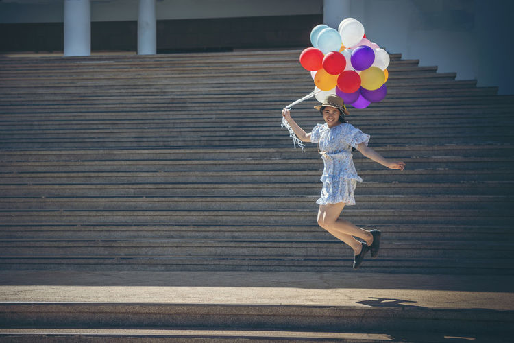 Full length of a woman holding balloons