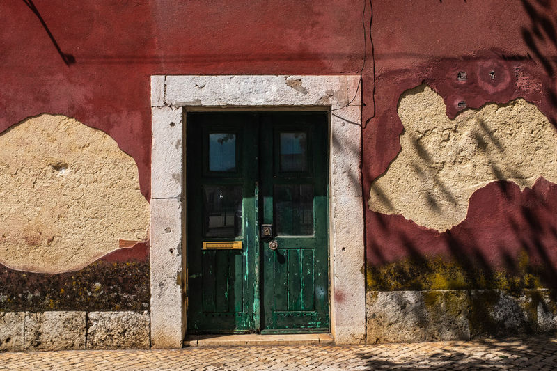 Closed door of old house in lisbon. the wall is deteriorated by rising damp and peeling plaster.
