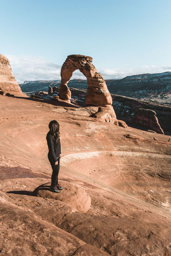 High Angle View Of Woman Standing On Rock Formation Against Sky