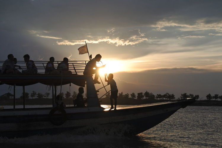 Silhouette people traveling on boat in lake against cloudy sky