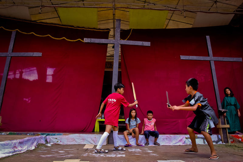 Children watch two others practice sword fighting at the town stage during a break from rehearsals for the Lenten Passion play in Paete, Laguna, the Philippines. The Philippines is an Asian country that is predominantly Roman Catholic, influenced by more than 300 years of Spanish rule starting in the 16th century. CHRIS QUINTANA Asian Culture Catholics Children Christianity Drama Holyweek Human Interest Lentenseason Passion Play Rural Life Rural Scene Sword Fight Young Men