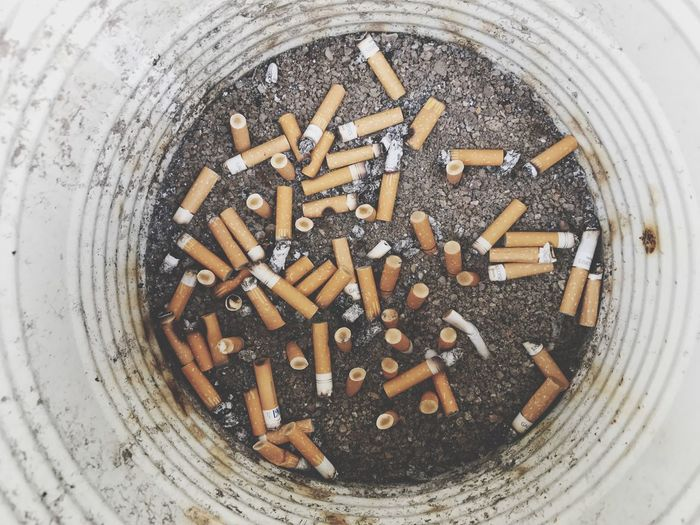 Directly Above Shot Of Cigarette Butts In Garbage Can