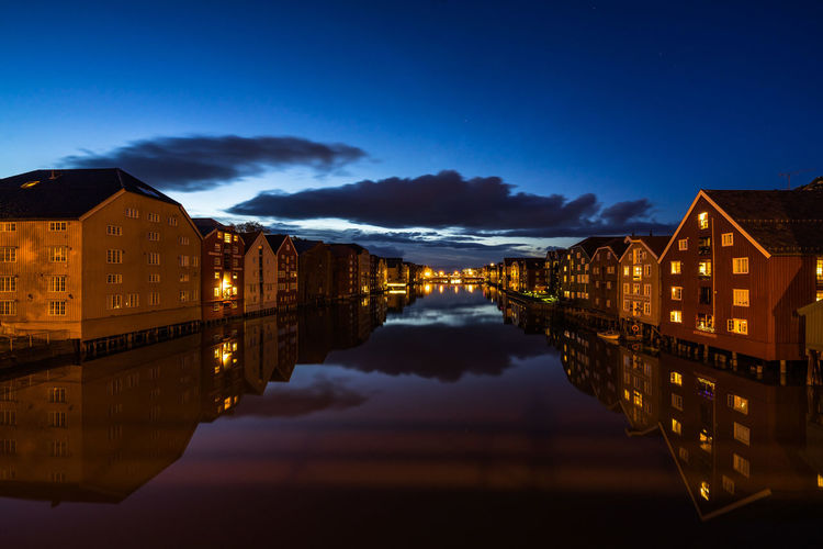 Twilight view of colorful wooden buildings on stilts along the Nidelva River, Trondheim, Norway Trondheim Norway Scandinavia Norwegian Northern Europe Reflection Sky Water Building Exterior Illuminated Architecture Night Cloud - Sky Waterfront No People Built Structure Building Nature Symmetry City Residential District Dusk Lake Blue Outdoors