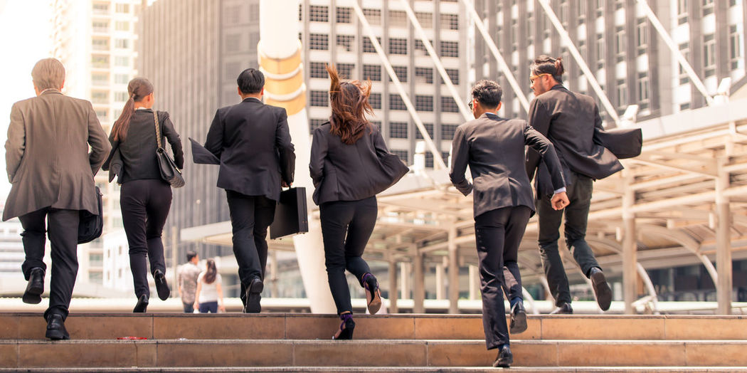 Rear View Of Businesspeople Running On Steps By Buildings In City