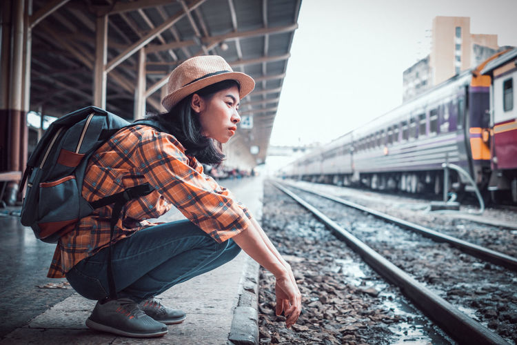 Young woman looking at train at railroad station
