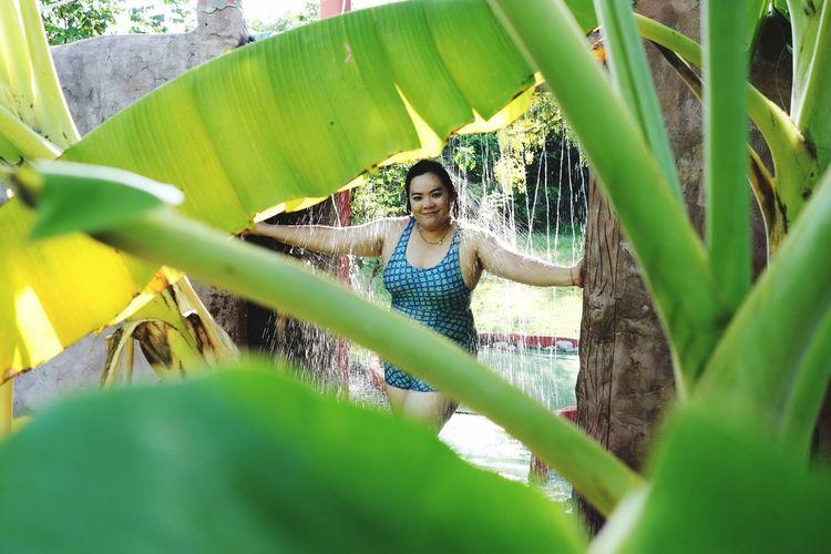 Portrait of smiling woman seen through plants standing under shower