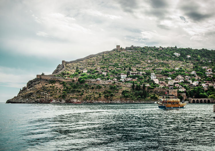 Scenic View Of Sea By Alanya Castle Against Cloudy Sky