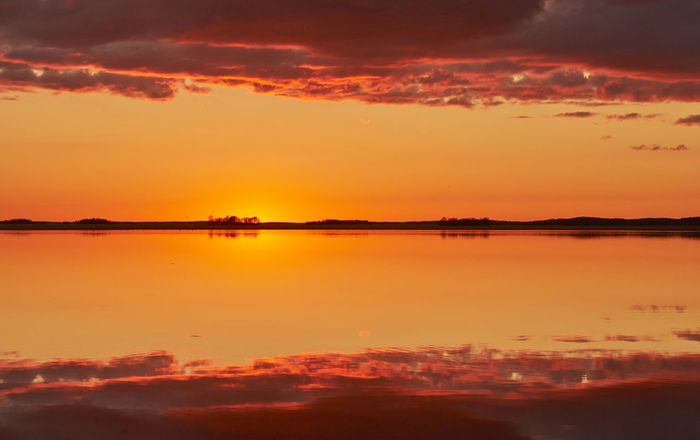 Dramatic sunset wth reflections in water Atmosphere Atmospheric Mood Beauty In Nature Calm Cloud - Sky Dramatic Sky Idyllic Lake Majestic Nature Orange Color Outdoors Reflection Romantic Sky Scenics Sea Sky Standing Water Sun Sunset Tranquil Scene Tranquility Vibrant Color Water Waterfront