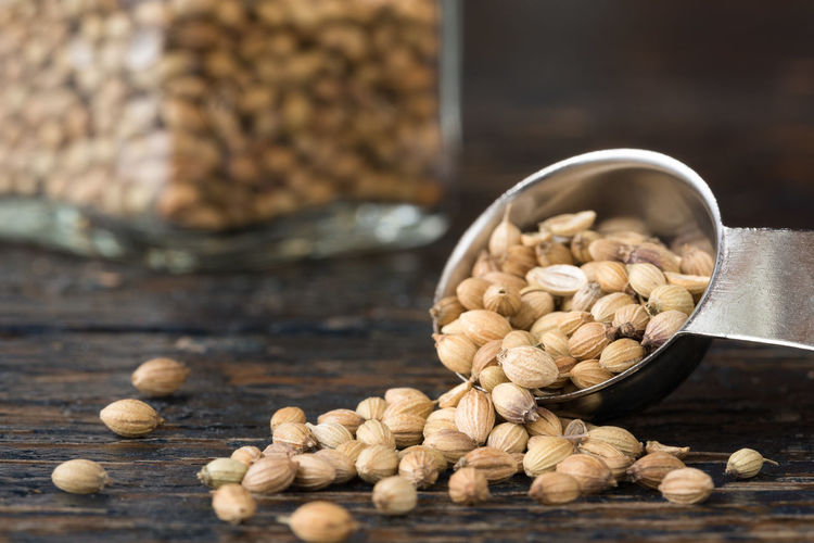 Close-up of coriander seeds spilling from bowl on wooden table