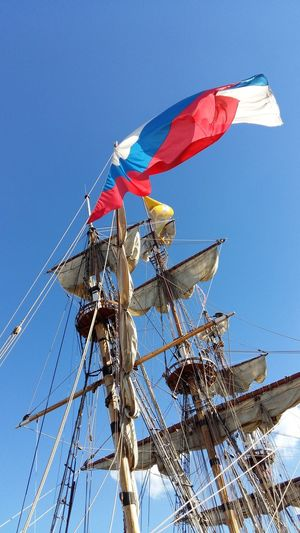 Low angle view of russian flag on mast against sky