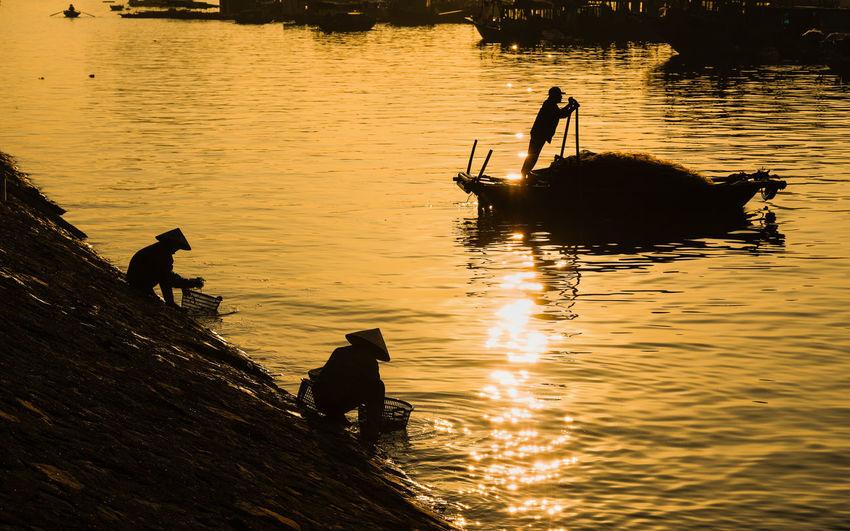 Silhouette people fishing in lake during sunset