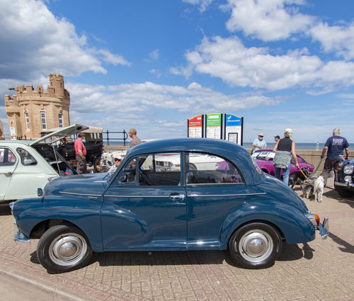 Architecture Blue Building Exterior Built Structure Car City Cloud - Sky Day Land Vehicle Large Group Of People Men Mode Of Transport Morris Minor Nature Outdoors People Police Force Real People Sky Transportation Women