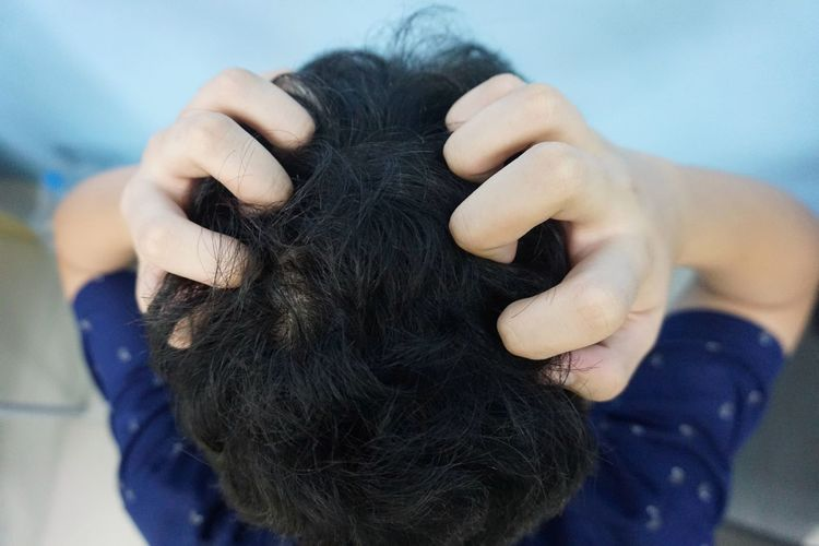 Close-up of frustrated boy scratching his head