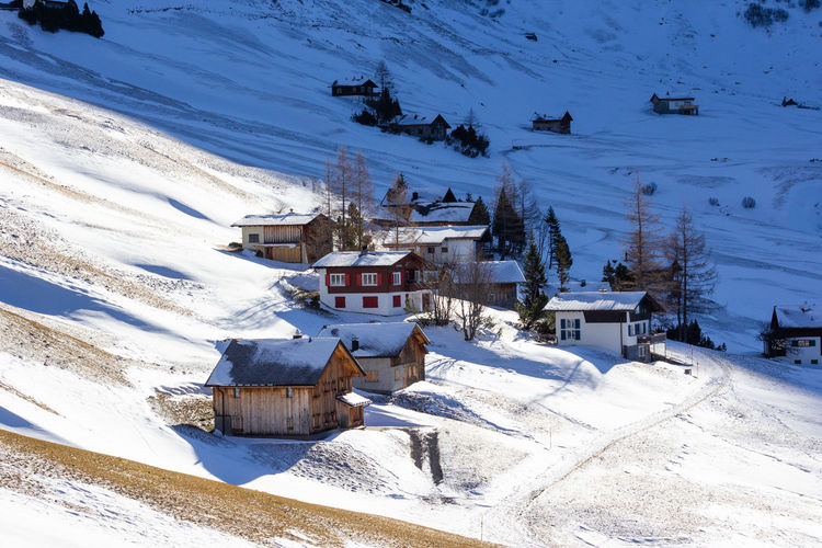 Houses on snow covered field by buildings