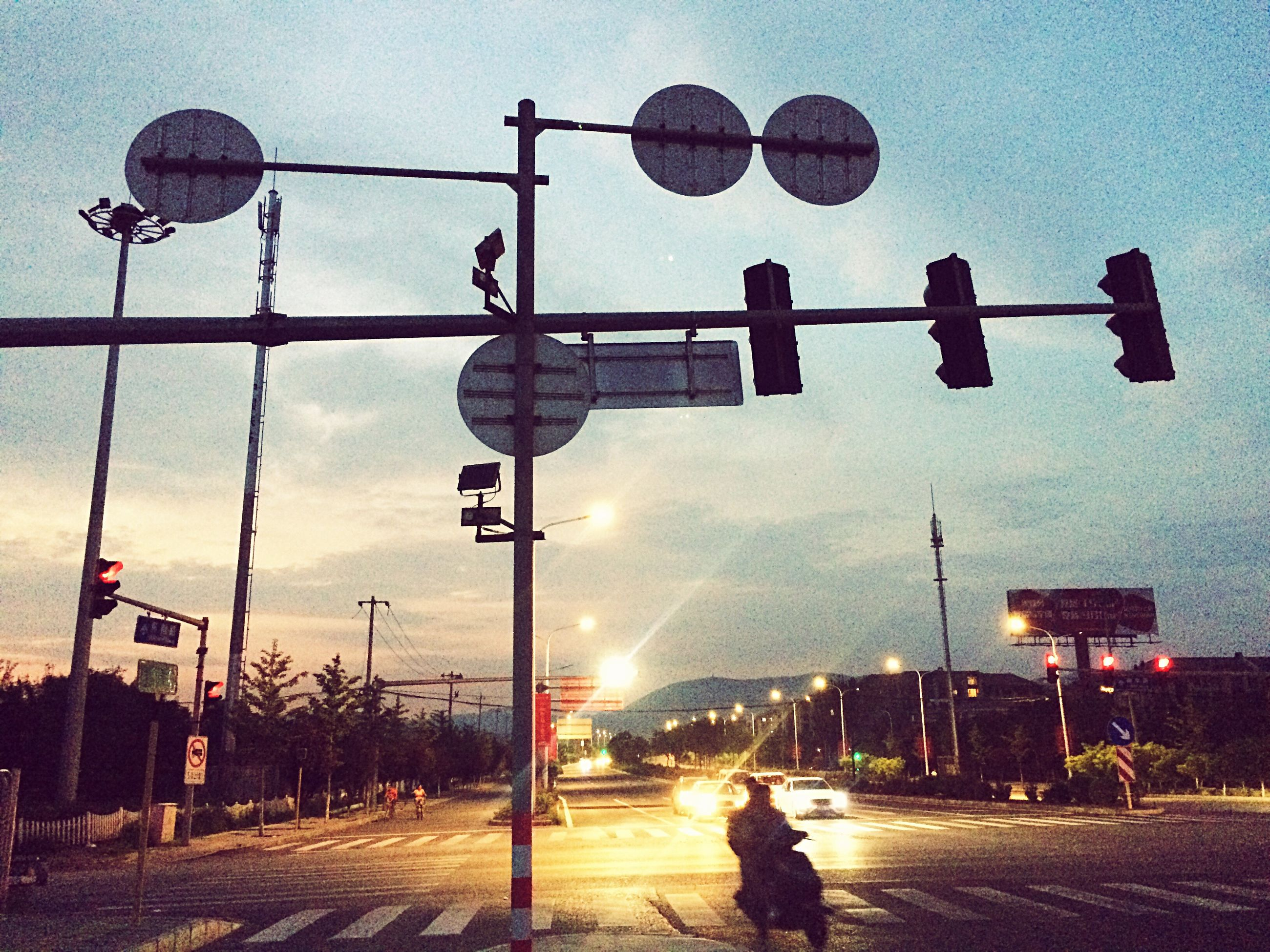 street light, traffic signal, traffic light, road sign, communication, sky, stoplight, architecture, built structure, outdoors, building exterior, signal, day, city, no people
