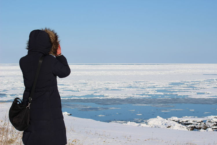 Rear view of woman looking at frozen lake against clear blue sky