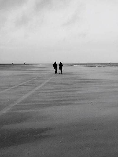 Rear view of man and woman standing at beach