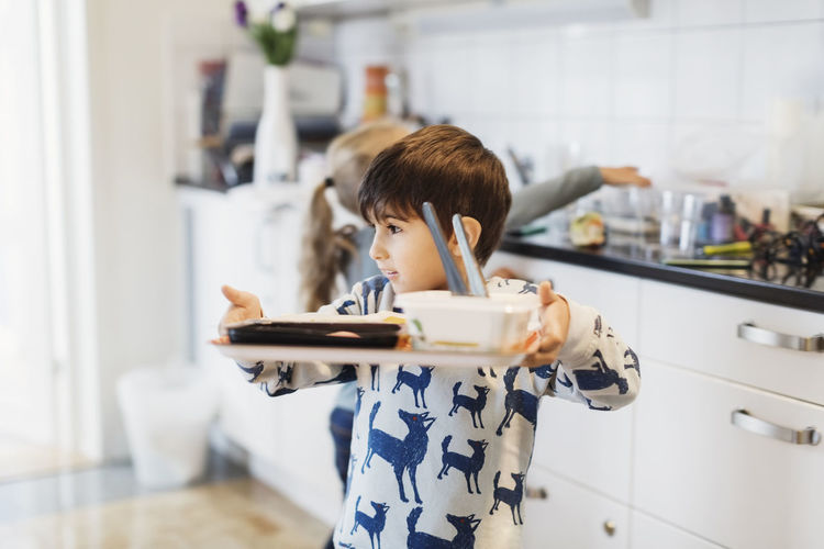 Portrait of boy holding camera at home