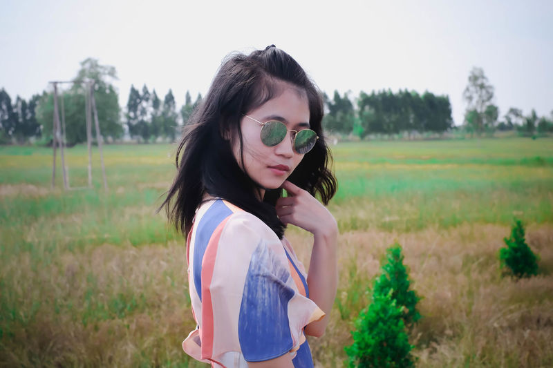 Young woman wearing sunglasses standing on field
