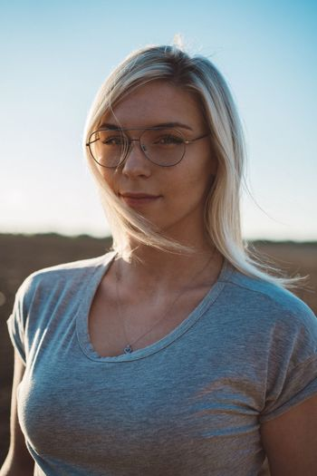 Portrait of young woman against clear sky