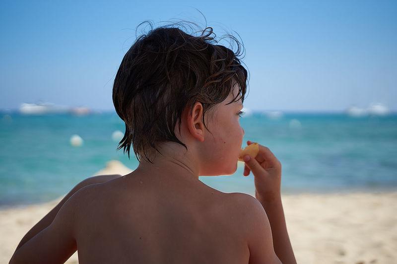 Rear view of shirtless boy eating food at beach